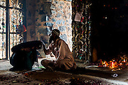 19th March 2015, New Delhi, India. A Sufi 'pir' (master) performs a cleansing rite on a female supplicant in the ruins of Feroz Shah Kotla in New Delhi, India on the 19th March 2015<br /> <br /> PHOTOGRAPH BY AND COPYRIGHT OF SIMON DE TREY-WHITE a photographer in delhi<br /> + 91 98103 99809. Email: simon@simondetreywhite.com<br /> <br /> The13th century fortress-city of Firoz Shah Kotla in Delhi is thronged weekly with thousands of supplicants seeking favour from supernatural beings of smokeless fire, - Djinns. These magical entities also known as Jinn, Jann or Genies spring from Islamic mythology as well as pre-Islamic Arabian mythology. They are mentioned frequently in the Quran and other Islamic texts and inhabit an unseen world called Djinnestan. Believers, mostly Muslim but from other faiths too, circumnavigate the ruins clutching dozens of photocopied requests, flower petals, incense, and candles. They visit the numerous niches and alcoves in the catacombs said to be occupied by different djinns and greet and salute the invisible occupants with offerings.  A copy of their requests, often with detailed contact information, photographs and even police reports to bolster the case is left with the 'Baba' before moving on to the next where the procedure is repeated - like making applications at different departments of a bureaucracy.