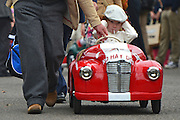 © Licensed to London News Pictures. 15/09/2013. Chichester, UK A young driver covers their ears whilst passing a loud engine. Young competitors return to there paddock  sucking lollipops after completing in the Settrington Cup. People enjoy the atmosphere at the last day of 2013 Goodwood Revival. The event recreates the glorious days of motor racing and participants are encouraged to dress in period dress. The revival is the only event of its kind to be staged entirely in the nostalgic time capsule of the 1940s, 50s and 60s Photo credit : Stephen Simpson/LNP.