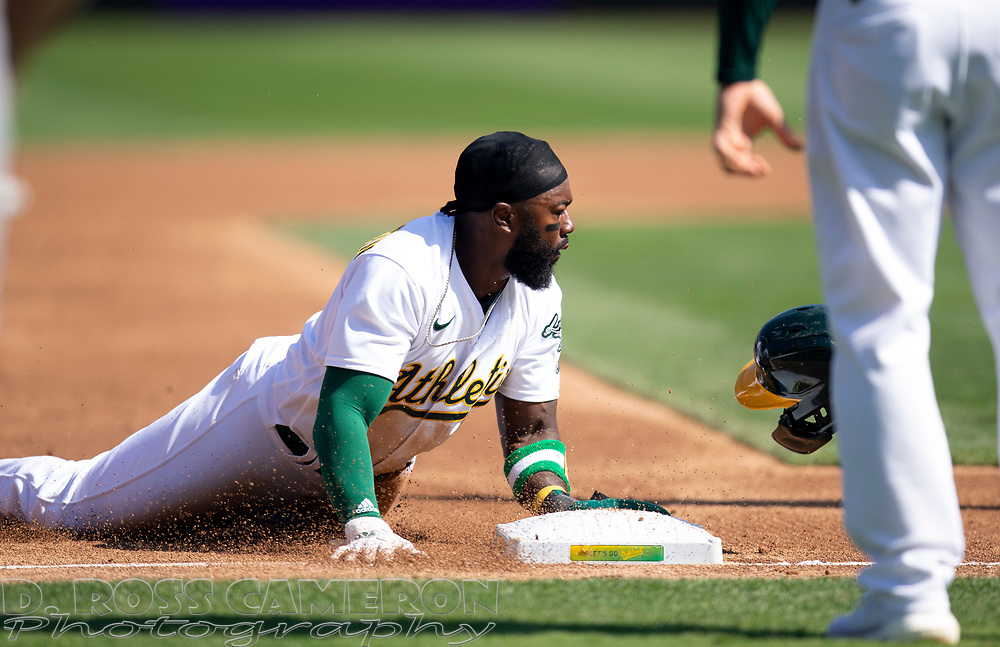 Sep 26, 2021; Oakland, California, USA; Oakland Athletics shortstop Josh Harrison (1) slides safely into third base after tagging up on a fly ball to right field by Mark Canha against the Houston Astros in the third inning at RingCentral Coliseum. Mandatory Credit: D. Ross Cameron-USA TODAY Sports