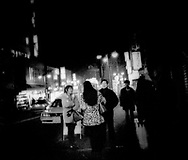 A Japanese man (r) negotiates with a Thai mama-san (l) to have sex in a so-called love hotel nearby with a young Thai street prostitute wearing a fake leopard-skin coat on a wintry night in Tokyo's Shin-Okuba, Japan.