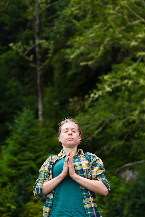 A girl meditates on the beach at Thrasher Cove, West Coast Trail, British Columbia, Canada.