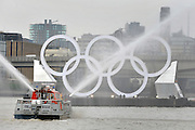 © Licensed to London News Pictures. 28/02/2012, London, UK. A fire boat shoots water from its hoses in celebration of the occasion. Giant Olympic rings measuring 11 metres high by 25 metres wide are floated down the River Thames on a barge, marking 150 days to go to the start of the London 2012 Olympic and Paralympic Games. Photo credit : Stephen Simpson/LNP