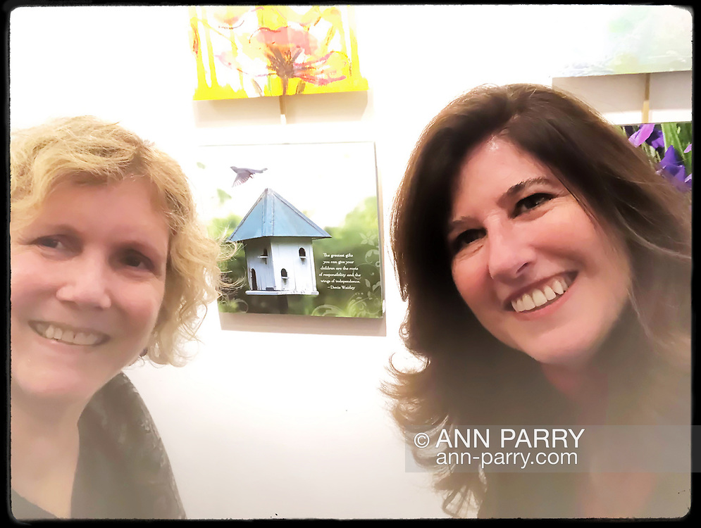 Manhasset, New York, U.S., December 7, 2019. L-R, photographers ANN PARRY and DIANE LUGAR flank Lugar's photograph of birdhouse at Reception for The Art Guild exhibition, held at historic Elderfields Preserve.