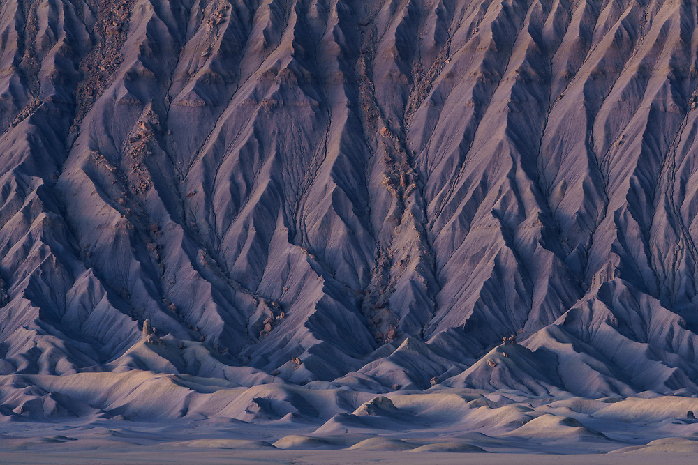 Soft wilight colors illuminate the fluted patterns of the eroded badlands of Factory Butte, Utah, USA