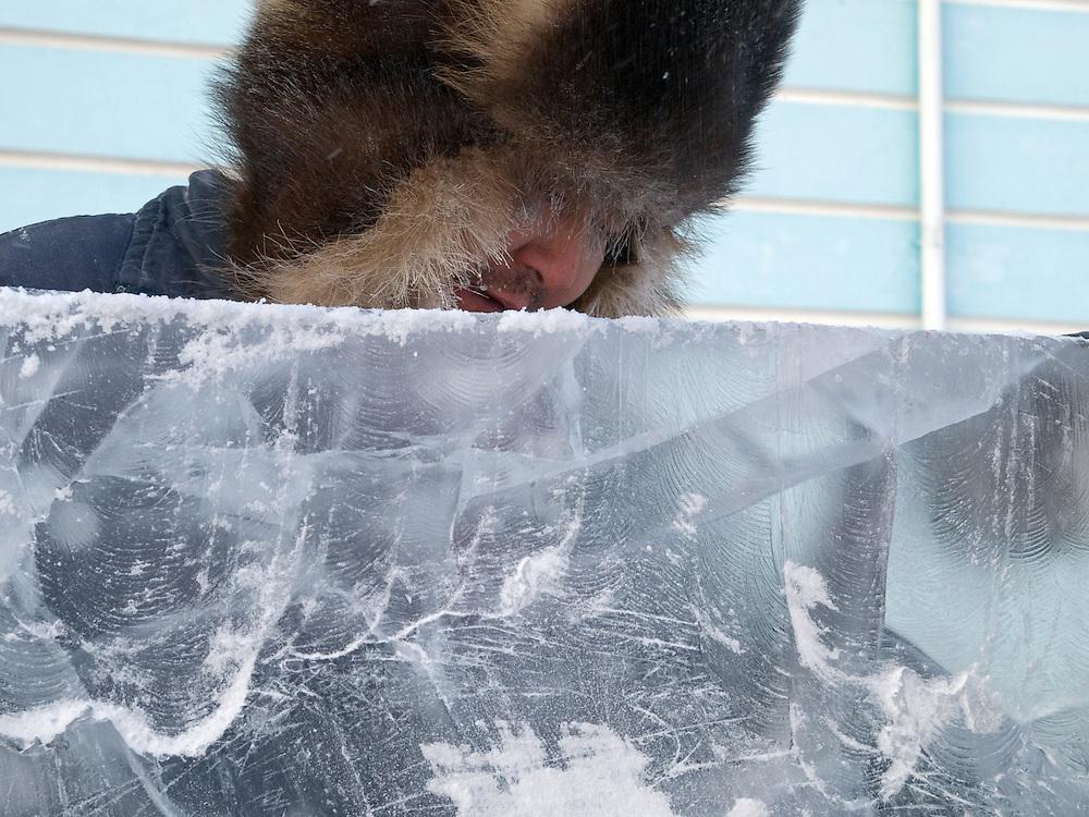 Einwohner von Jakutsk mit traditioneller Pelzmuetzte geschuetzt gegen die extrem Kaelte von ueber -30 Grad Celsius bearbeitet einen Eisblock. Jakutsk hat 236.000 Einwohner (2005) und ist Hauptstadt der Teilrepublik Sacha (auch Jakutien genannt) im Foederationskreis Russisch-Fernost und liegt am Fluss Lena. Jakutsk ist im Winter eine der kaeltesten Grossstaedte weltweit mit durchschnittlichen Winter Temperaturen von -40.9 Grad Celsius. Die Stadt ist nicht weit entfernt von Oimjakon, dem Kaeltepol der bewohnten Gebiete der Erde.<br /> <br /> Portrait of a Yakutsk inhabitant protected with the traditional fur cap and warm clothing against the extrem cold - doing ice sculptures. Yakutsk is a city in the Russian Far East, located about 4 degrees (450 km) below the Arctic Circle. It is the capital of the Sakha (Yakutia) Republic (formerly the Yakut Autonomous Soviet Socialist Republic), Russia and a major port on the Lena River. Yakutsk is one of the coldest cities on earth, with winter temperatures averaging -40.9 degrees Celsius.