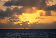 Caribbean beach at sunset with ocean and clouds