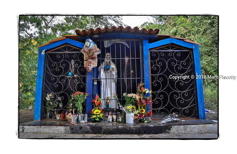 SHOT 2/3/18 4:38:08 PM - A capilla dedicated to Santa Muerte (Nuestra Señora de la Santa Muerte) near El Guamuchil, Mexico. Santa Muerte (Holy Death), is a female deity (or folk saint depending on school of thought) in Mexican folk religion, particularly Folk Catholicism, venerated primarily in Mexico and the Southwestern United States. A personification of death, she is associated with healing, protection, and safe delivery to the afterlife by her devotees. Despite condemnation by the Catholic Church her devotees have grown in numbers lately and many followers of Santa Muerte live on the margins of the law or outside it entirely.  In the Mexican and U.S. press, the Santa Muerte cult is often associated with violence, criminality, and the illegal drug trade. Altars of Santa Muerte temples generally contain one or multiple images of the Lady, generally surrounded by any or all of the following: cigarettes, flowers, fruit, incense, water, alcoholic beverages, coins, candies and candles. Capillas are common along the roads and highways of Mexico which is heavily Catholic and are often dedicated to certain patron saints or to the memory of a loved one that has passed away. Often times they contain prayer candles, pictures, personal artifacts or notes. (Photo by Marc Piscotty / © 2018)