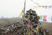 The stupa and prayer flags at the top of the Nachung-La mountain pass (4153m) between the Brokpa villages of Merak and Sakteng, Eastern Bhutan. Prayer flags are ubiquitous in Bhutan often found fluttering on mountain passes. They come in five colours - blue, green, red, yellow and white - symbolising the elements of water, wood, fire, earth and iron.