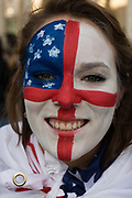 Seen in a close-up detail, we see a young woman's face, painted with an amalgamation of both the US and English flags during both countries opening World Cup group match. Having walked through Trafalgar Square, the location for many a sporting celebration and protest, the woman smiles to the viewer, her even teeth showing and hair brushed away from her face. But her allegiance is divided, a split loyalty for this football fan who is an American citizen but who lives in London - and so supports both teams. The blue and white Stars and Stripes appear in the top left corner and the red cross of St George horizontally across her cheeks and vertically down her nose.