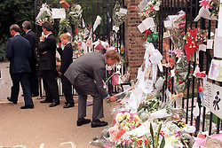 Prince William lays flowers given by a wellwisher in amongst the hunderds of bunches already laid outside Kensington Palace - his mother Diana, Princess of Wales's offical residence -  in London this afternoon as his father, the Prince of Wales and brother, Prince Harry leave the gates (left).  The family had arrived in London from Balmoral earlier today in preparation for the Princess's funeral at Westminster Abbey tomorrow morning.  POOL PHOTO BY REBECCA NADEN/PA