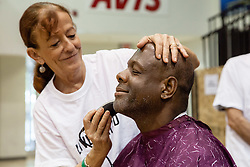 Theresa Morey provides David A. James with a fresh cut and shave.  Project Homeless Connect  connects those in need of support with vital resources and services.  St. Thomas, USVI.  4 December 2015.  © Aisha-Zakiya Boyd