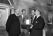 22/08/1966<br /> 08/28/1966<br /> 22 August 1966<br /> Blackrock College R.F.C. press conference at Stradbrook Road, Blackrock, Dublin. To announce the First ever Festival of Rugby at Blackrock College to be played on the 11 September 1966 on the Club's new grounds, the trophy was donated by Blackrock College. . Picture shows Very Rev. Tim O'Driscoll, C.S.Sp., (left) President of Blackrock College handing over the new trophy for the Festival to Mr. J. Sadleir, (right) President of Blackrock College R.F.C., at the reception at the new grounds. Also in the picture are Mr. N.H. Brophy, Club Captain (1966/67) and Mr. Noel Turley, (Chairman of the Festival Committee).