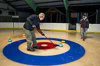 """Jim Bobotas sweeps his team mates stone closer to the """"button"""" to score for the blue team during the first night of curling at the Arthur Tilton Ice Rink with Gilford Parks and Rec on Thursday evening.  (Karen Bobotas/for the Laconia Daily Sun)"""