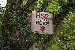 Harefield, UK. 27th April 2019. A sign placed by environmental activists from Colne Valley Action sitting in trees to prevent their felling as part of work scheduled for this weekend for the HS2 project. The Colne Valley is an area of natural beauty and large areas of trees have been felled there for HS2 in recent weeks. Protesters based at the Harvil Road Wildlife Protection Camp are seeking to prevent further destruction.