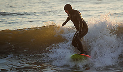 © Licensed to London News Pictures. <br /> 09/05/2016. <br /> Saltburn by the Sea, UK.  <br /> <br /> Surfer Jim Fisher rides a wave as the sun rises over the coastline at Saltburn by the Sea in North Yorkshire. After the warmest day of the year yesterday temperatures are due to drop slowly over the rest of the week.<br /> <br /> Photo credit: Ian Forsyth/LNP