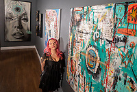 Jenn Hampton is the co-owner of the Parlor Gallery in Asbury Park. She is pictured with art by Porkchop (at left, vertical) and two pieces by Rob Santello. Photo was taken on March 5, 2020.