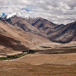 Small green valley with dry mountains all around on the way to Pangong Lake.