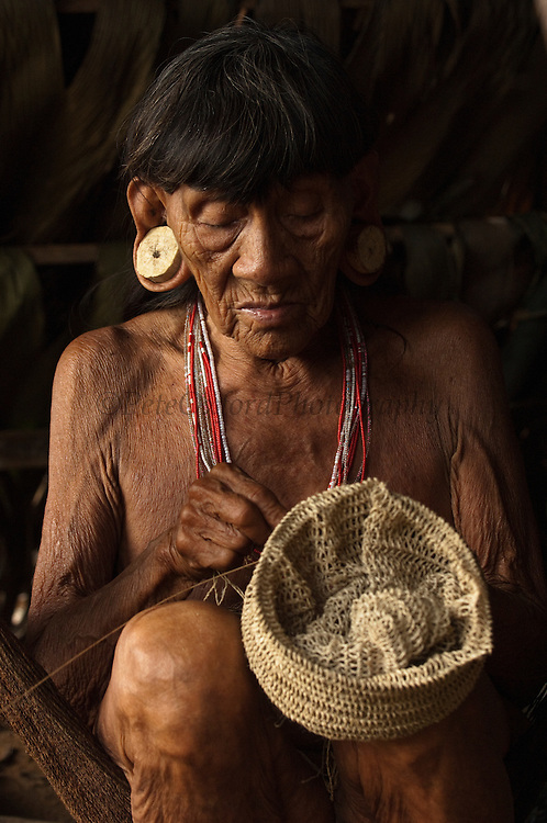 Huaorani Indian woman - Konta ñamaronko making a shigra. Gabaro Community. Yasuni National Park.<br /> Amazon rainforest, ECUADOR.  South America<br /> Shigras are hand-knotted bags made from a fibre extracted from a palm leaf. The fibre is dryed and sun bleached before being rolled into sting for either bags or a thicker version for hammocks.<br /> She has the typical stretched ear lobes common amoung the Huaorani. They often wear balsa ear plugs.<br /> This Indian tribe were basically uncontacted until 1956 when missionaries from the Summer Institute of Linguistics made contact with them. However there are still some groups from the tribe that remain uncontacted.  They are known as the Tagaeri. Traditionally these Indians were very hostile and killed many people who tried to enter into their territory. Their territory is in the Yasuni National Park which is now also being exploited for oil.