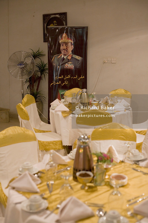 A banner portrait of the Sudanese President, Omar Hassan Ahmad al-Bashir near the laid tables that are ready for a buffet dinner in the offices and showroom for Sudanese Womens' General Union activity project in central Khartoum.