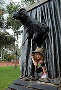 """Child (6 years old) crawling through """"Curtain Call"""" sculpture by Les Kossatz. Darling Harbour, Sydney, Australia"""