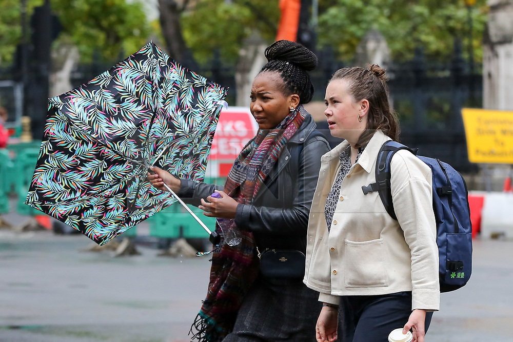 © Licensed to London News Pictures. 16/10/2019. London, UK. A woman struggles to control her umbrella in Westminster, London. According to the Met Office more rain is forecasted for the next few days. Photo credit: Dinendra Haria/LNP
