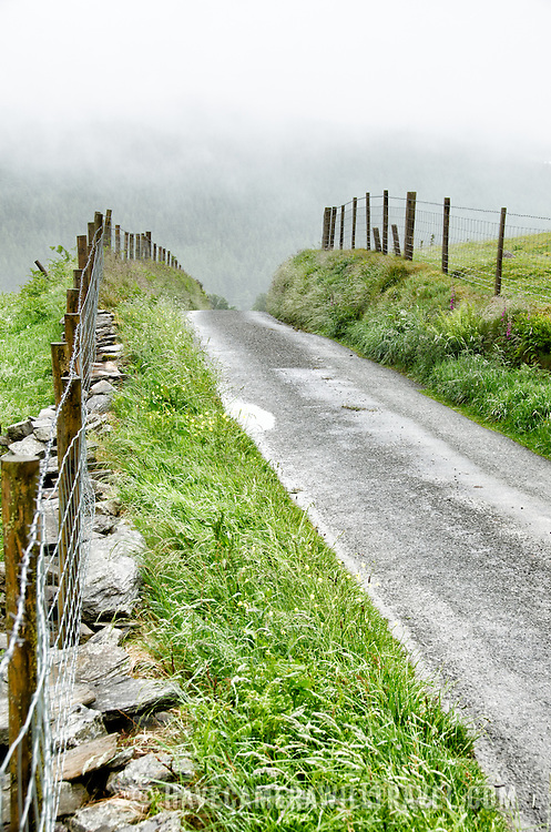 A small country lane running through the farms on top of a misty plateau in Snowdonia, Wales.