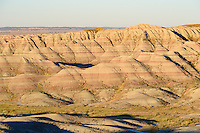 Early morning sunlight illuminates a striated portion of the badlands in South Dakota.