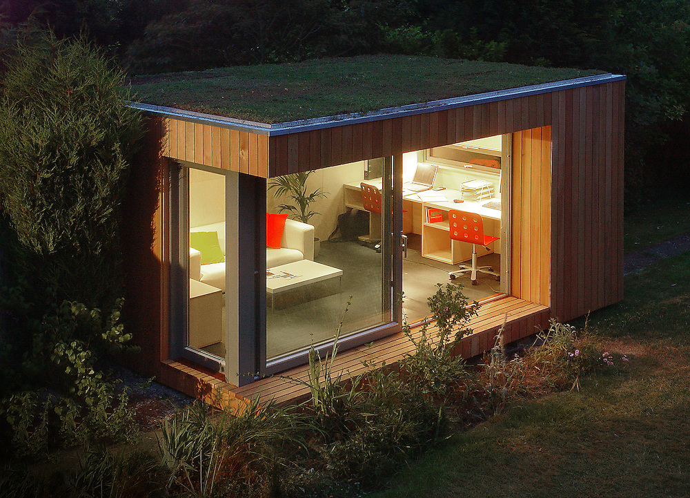 outdoor office with grass roof in garden at night