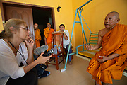 Buddhist head monk attending the funeral ceremonial lunch in a village near Siem Reap, Cambodia for a 34 year old mother of 3 who died of a heart attack the day before while washing the family's breakfast dishes. Attended by family and friends and neighbors. A tent and shrine and funeral preparations are made in the family yard.