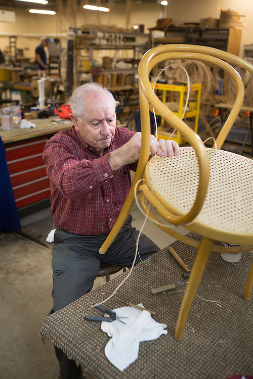 Edward Fernandez of Madison restores the caning on a chair at the Sage Eldercare furniture restoration workshop in Summit.  1/5/14 Photo by John O'Boyle
