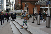A young woman steps down while carrying her pet dog outside Liverpool Street Station, on 16th February 2017, in the City of London, England.