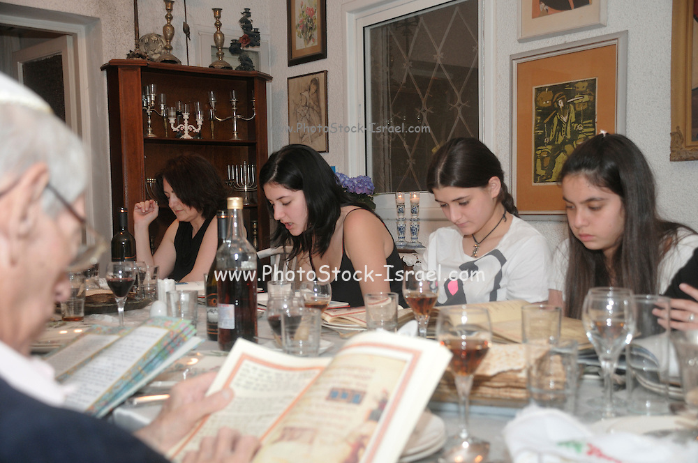 """family sitting around a table set for a Jewish Festive meal on Passover (transliterated as Pesach or Pesah), also called chag HaMatzot - Festival of Matzot is a Jewish holiday beginning on the 15th day of Nisan, which falls in the early spring and commemorates the Exodus and freedom of the Israelites from ancient Egypt. Passover marks the """"birth"""" of the Jewish nation, as the Jews were freed from being slaves of Pharaoh and allowed to become servants of God instead."""