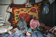 Aisha A, 28, left, and her roommate, Fatima, 20, sit on a mattress in their tent in an IDP camp, Maiduguri, Nigeria, April 26, 2019. Aisha was abducted by seven BH fighters in Gwoza Local Government in 2014. After she was taken to a commander's house, she was raped by him and became the fourth wife. She stayed in his home for a year and eight months, but did not get pregnant. Aisha got pregnant by an IDP man in the same camp with whom she married, and gave birth to a boy a day after this photo was taken. Also pregnant, Fatima was abducted by BH fighters when she was 15 years old. She was forced to marry a commander and gave birth to a son in 2017 whom she left in the forest. She realized she was pregnant again after escaped. Fatima gave birth to a boy ten days after this photo was taken.