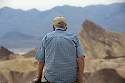 Old man contemplating Zabriski point, part of Amargosa Range located in Death Valley National Park in California, noted for its erosional landscape and being one of the worlds hottest places. The location was named after Christian Brevoort Zabriskie, vice-president and general manager of the Pacific Coast Borax Company in the early 20th century. The company's twenty-mule teams were used to transport borax from its mining operations in Death Valley.