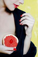 beautiful caucasian woman portrait  showing grapefruit breast studio on yellow background