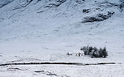 Winter snow  scene of cottage at base of Buachaille Etive Mor mountain near Glen Coe in Scotland, UK
