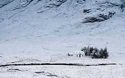 Winter snow  scene of cottage at base of Buachaille Etive Mor mountain near Glen Coe in Scotland, UK