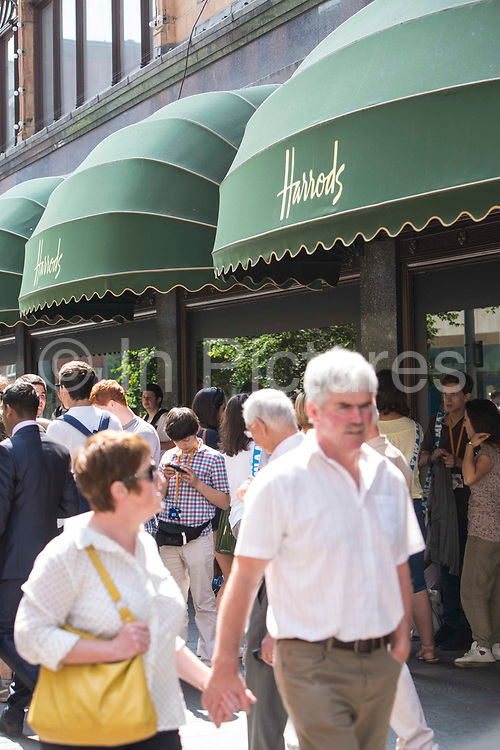 Shoppers and tourists outside the world famous Harrods department store in Knightsbridge, London, United Kingdom.
