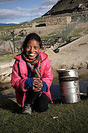 India, Ladakh. Nilza, 12-years old girl from Korzok washing the dishes in one of the streams.