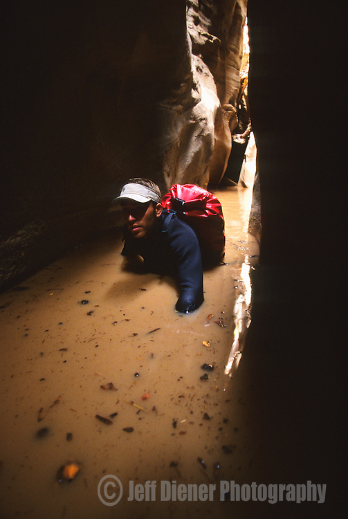 A young man wades through deep water while canyoneering in Zion National Park, Utah.
