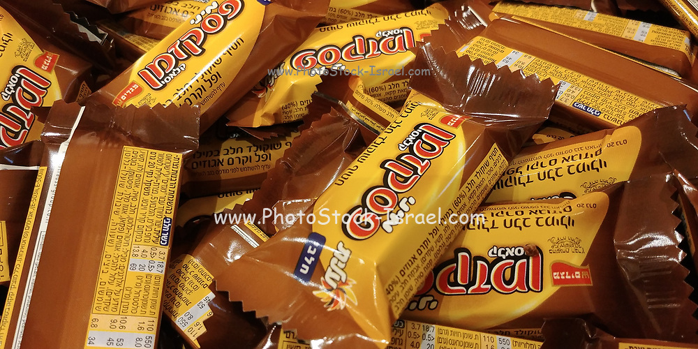 A large stack of Pesek Zman (time out) Israeli mini wafer coated Chocolate bars with Hebrew text
