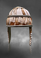 Minoan boar's tusk helmet with cheek guards,1450-1300 BC, Heraklion Archaeological Museum, grey background<br /> <br /> This restored boars tusk helmet was described in Homers Iliad being worn by Cretan hero Meriones. It bis believed that the helmet was ceremonial depicting the rank of an officer, grey background .<br /> <br /> If you prefer to buy from our ALAMY PHOTO LIBRARY  Collection visit : https://www.alamy.com/portfolio/paul-williams-funkystock/minoan-art-artefacts.html . Type -   Heraklion   - into the LOWER SEARCH WITHIN GALLERY box. Refine search by adding background colour, place, museum etc<br /> <br /> Visit our MINOAN ART PHOTO COLLECTIONS for more photos to download  as wall art prints https://funkystock.photoshelter.com/gallery-collection/Ancient-Minoans-Art-Artefacts-Antiquities-Historic-Places-Pictures-Images-of/C0000ricT2SU_M9w