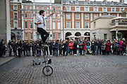Street performer with a tall unicycle thrills the gathered crowd with his performance in Covent Garden, London, England, United Kingdom.