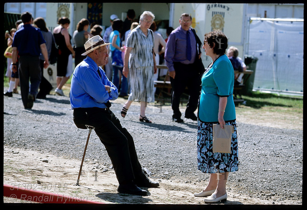 Man sits on convertible walking stick talking to woman at fairgrounds of the annual National Eisteddfod culture fest; Meifod, Wales.