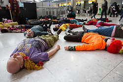 Campaigners against airport expansion from Rising Up stage a flashmob die-in at Heathrow Airport's Terminal 2 on 18th February 2017 at Heathrow, United Kingdom. The activists were protesting against proposals to build a third runway at Heathrow Airport in order to permit an additional 250,000 flights a year.