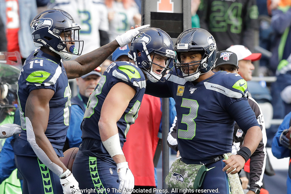 Seattle Seahawks quarterback Russell Wilson (3) greets tight end Jacob Hollister, center, after Wilson passed to Hollister for touchdown against the Tampa Bay Buccaneers during the first half of an NFL football game, Sunday, Nov. 3, 2019, in Seattle. Seahawks wide receiver DK Metcalf looks on at left. (AP Photo/John Froschauer)
