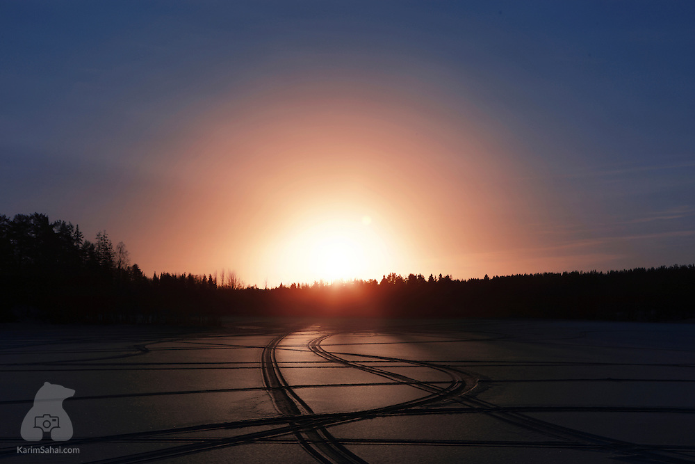 Snowmobile tracks on a frozen lake at sunrise, Lappland, Sweden.
