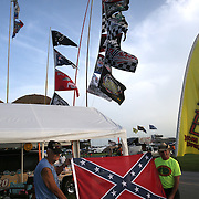 Larry, a U.S. war veteran, and Jim the Jackman (right) pose with their Confederate flag at their camp in the infield during the 57th Annual NASCAR Coke Zero 400 practice session at Daytona International Speedway on Friday, July 3, 2015 in Daytona Beach, Florida.  (AP Photo/Alex Menendez)
