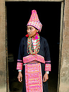 A married Ko Pala ethnic minority woman wears her traditional costume at home, Ban Honglerk, Phongsaly Province, Lao PDR. The brightly coloured, flamboyant costumes of the young Pala women are in contrast to the more conservative clothing of their elders. One of the most ethnically diverse countries in Southeast Asia, Laos has 49 officially recognised ethnic groups although there are many more self-identified and sub groups. These groups are distinguished by their own customs, beliefs and rituals.  Details down to the embroidery on a shirt, the colour of the trim and the type of skirt all help signify the wearer's ethnic and clan affiliations.