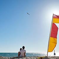 Surf lifesaving flag and couple at Cottesloe Main Beach